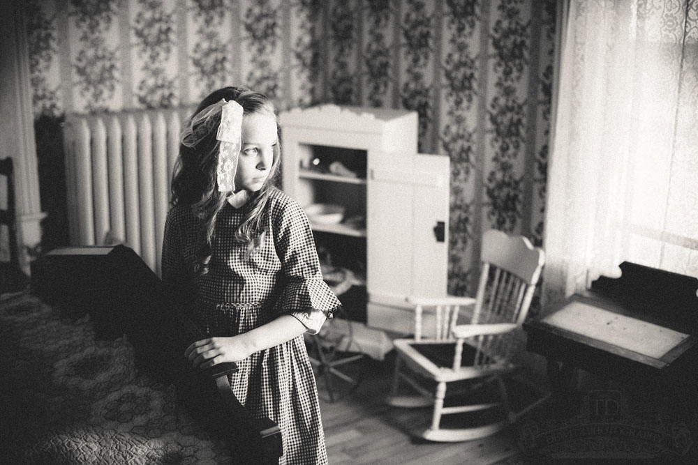 Teslyn at foot of bed in eerie early 1900s childs room