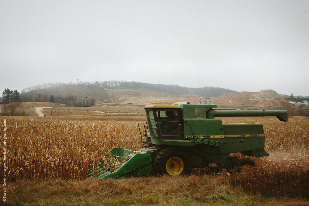 John Deere Combine Cuts Corn as Frac Sand is Mined From the Distant Hill - Sand Creek, WI