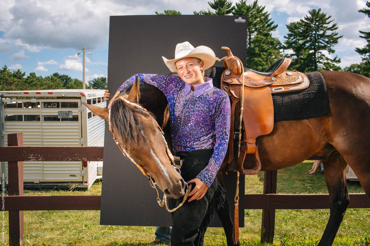 teen-cowgirl-poses-holding-horse-by-fence-portrait-northern-wisconsin-state-fair-2222