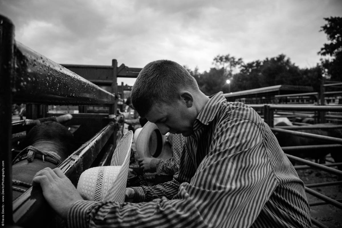 bull-rider-prays-before-rodeo-cowboy-hat-off-western-shirt-behind-the-chutes-in-the-rain-4611
