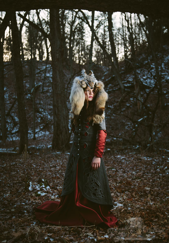 Model Red Riding Hood in the Woods With a Wolf Head