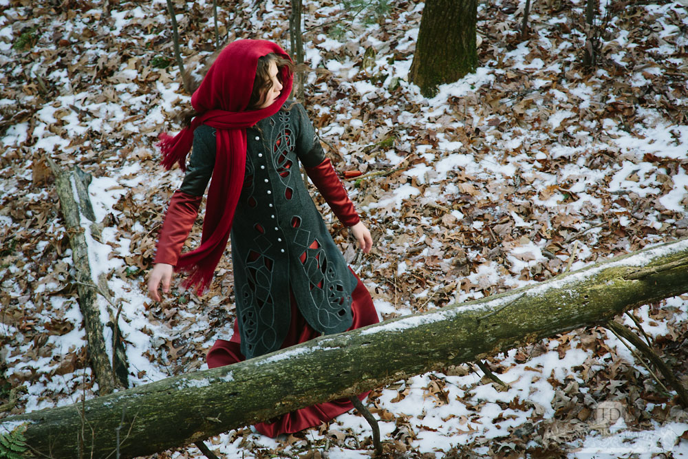 Red Riding Hood Looking Back by Log in Woods