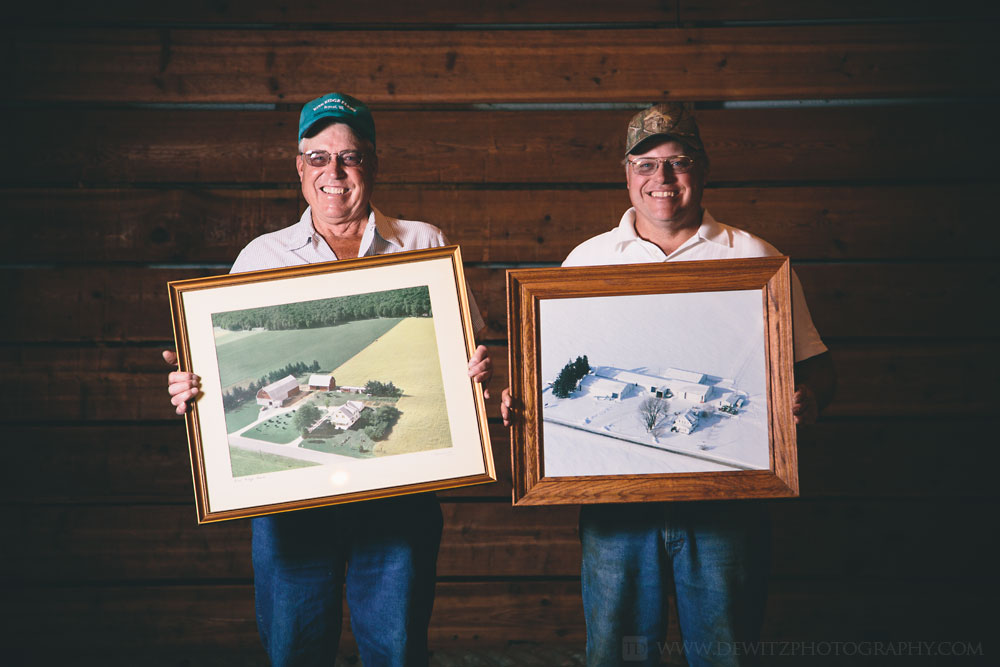 rine_farms_father_and_son_holding_aerial_photos_of_homestead