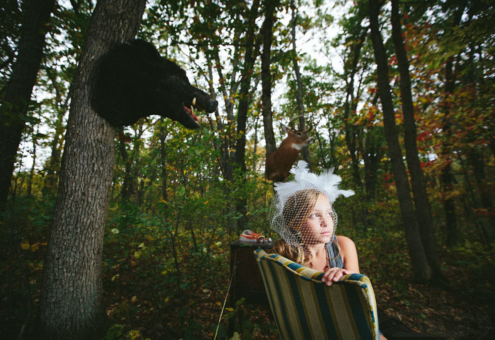 Teslyn in woods with boar mount and deer mount wearing birdcage vail