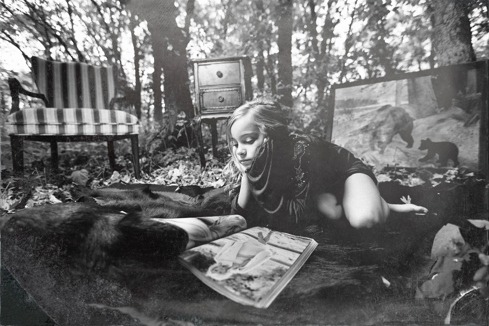 Teslyn on a bear rug in the woods reading Vogue magazine