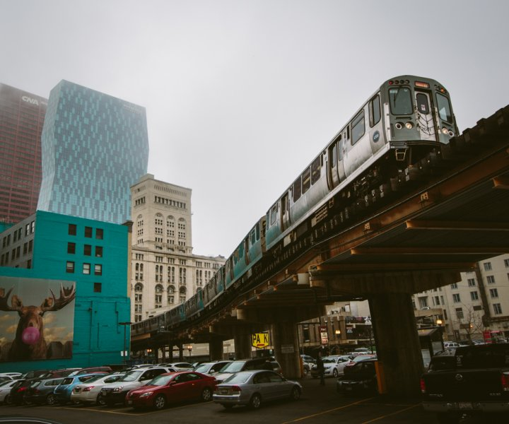 An Orange Line passenger train to Midway rolls through the elevated s-curved track just south of the loop. One of many unique billboards in Chicago over looks the parking lot from the side of a turquoise building of a moose blowing a pink bubble gum bubble.