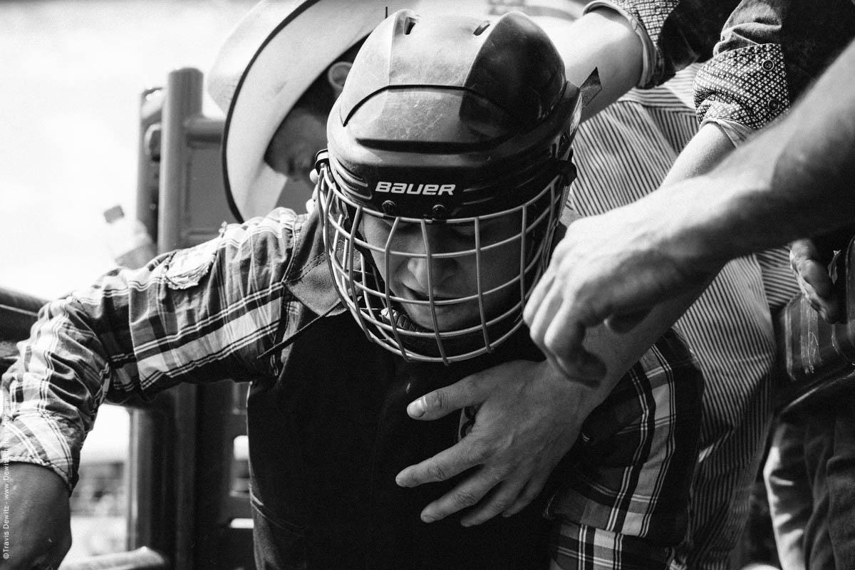 Bull Rider in Helmet Gets on Bull in Chute-2984