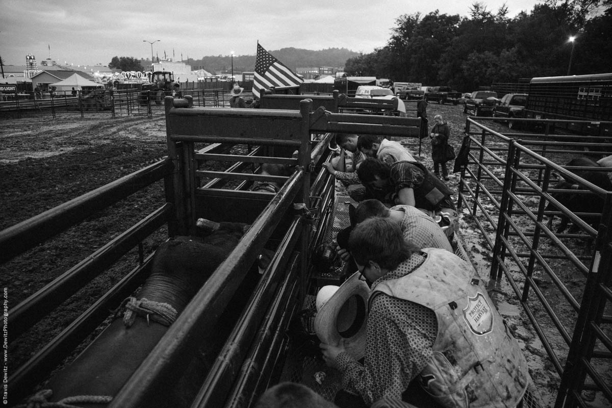 bull-riders-kneel-and-pray-behind-chutes-4610