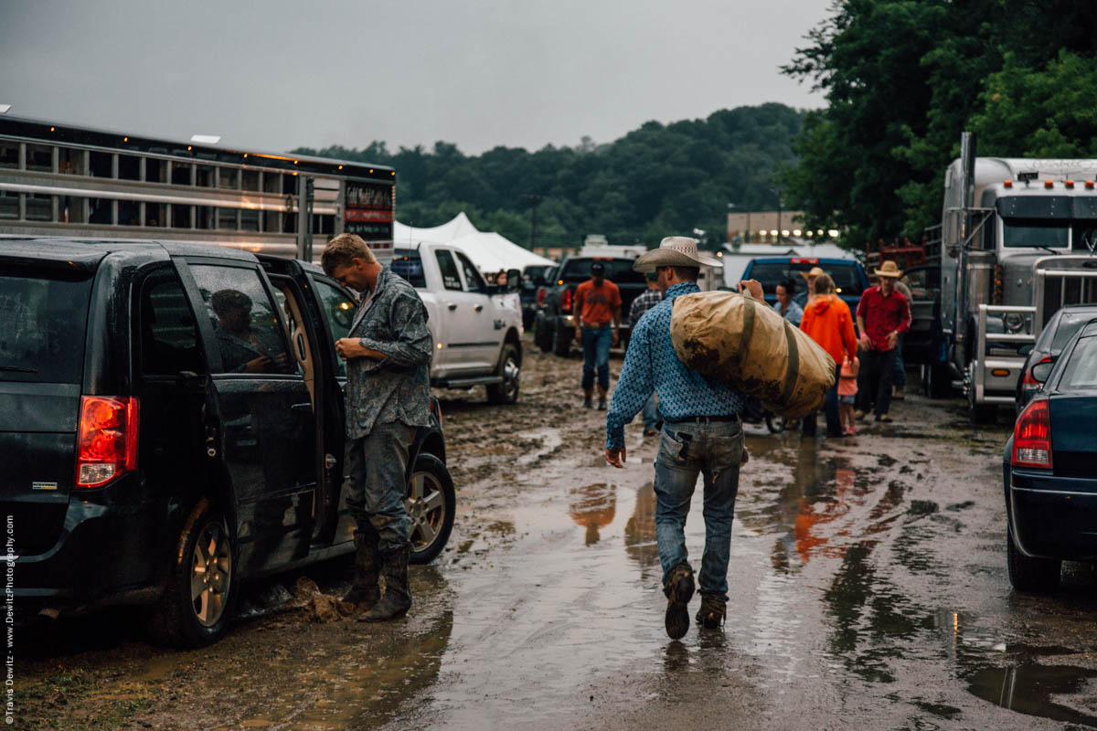 cowboys-carry-bags-getting-ready-for-rodeo-event-in-the-rain-4498
